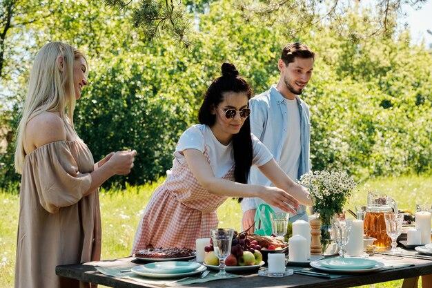 Due ragazze alla moda e un giovane uomo in piedi da tavola servita mentre una delle donne che mette un mazzo di fiori di campo in vaso prima di cena all'aperto