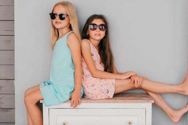 Due bambine alla moda in abiti colorati, seduta sul comò sul muro grigio