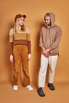 Due eleganti uomo e donna che si guardano l'un l'altro studiando, indossando abiti alla moda
