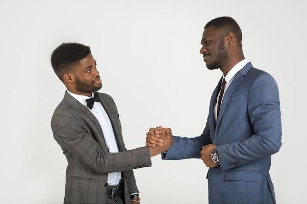 Due uomini alla moda in giacca e cravatta su uno sfondo grigio con una stretta di mano