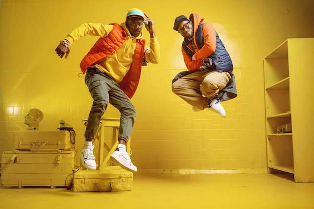 Due rapper alla moda con gioielli d'oro in un fantastico studio, artisti hip-hop con pareti gialle, cantanti rap alla moda, ballerini di break dance