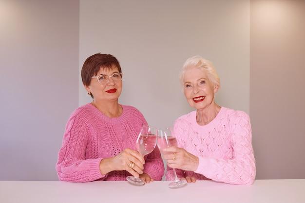 Due eleganti donne anziane in maglioni rosa sedute con bicchieri di vino al bar a parlare