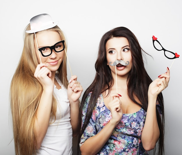 Due eleganti ragazze sexy migliori amiche pronte per la festa, su sfondo bianco