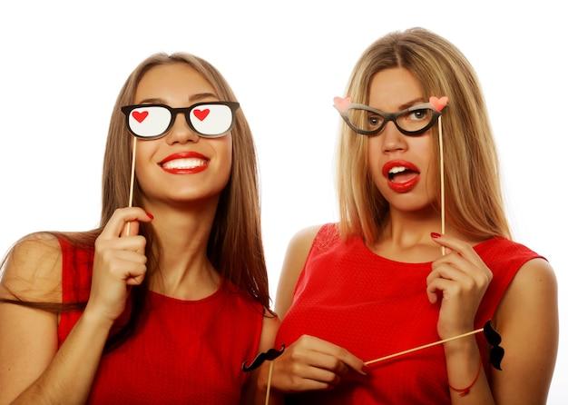 Due eleganti ragazze sexy migliori amiche che indossano un abito rosso pronto per la festa, su sfondo bianco