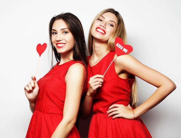Due migliori amiche di ragazze sexy eleganti che indossano abito rosso pronto per la festa, su sfondo bianco