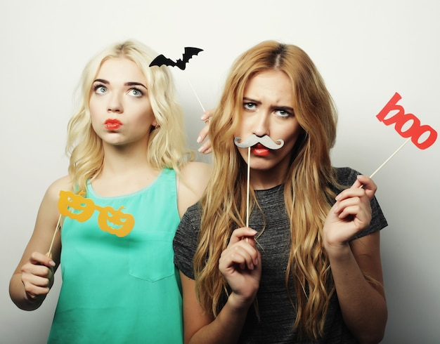 Due ragazze alla moda sexy hipster migliori amiche pronte per la festa, su sfondo grigio