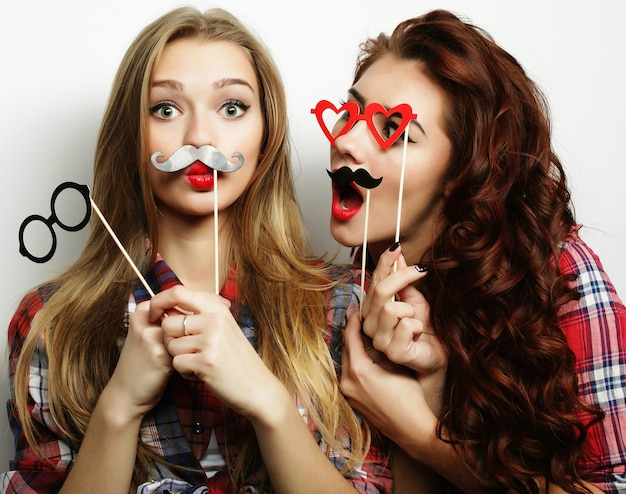 Due eleganti ragazze hipster sexy migliori amiche pronte per la festa, su sfondo grigio