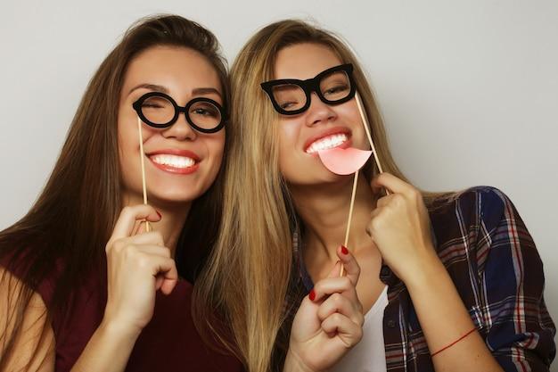 Due eleganti ragazze hipster sexy migliori amiche pronte per la festa, su sfondo grigio Foto Premium
