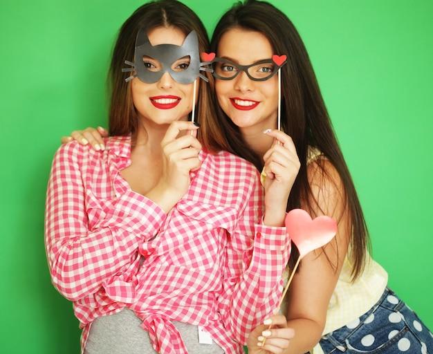 Due eleganti ragazze hipster sexy migliori amiche pronte per la festa, su sfondo verde