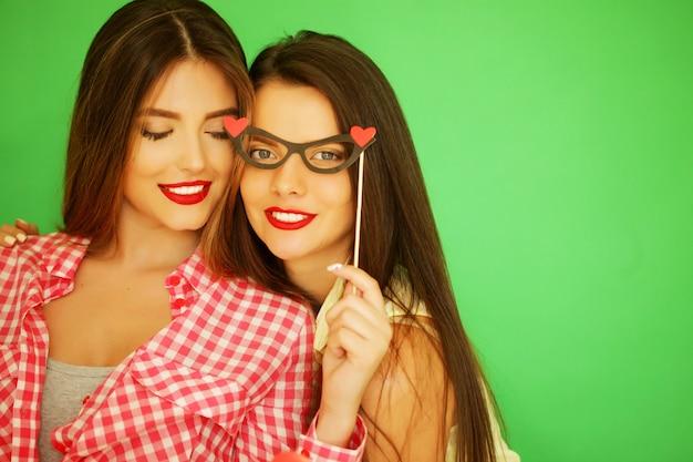 Due eleganti ragazze hipster sexy migliori amiche pronte per la festa, sul muro verde green