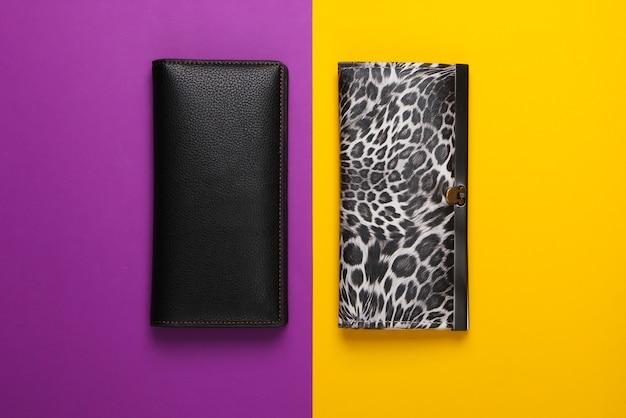 Due eleganti portafogli su giallo viola. minimalismo della moda.