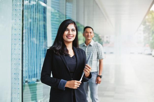 Due impiegati asiatici di successo che guardano avanti