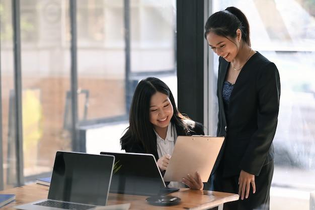 Due imprenditrici di successo che esaminano e analizzano il tasso di crescita degli investimenti in un ufficio moderno.