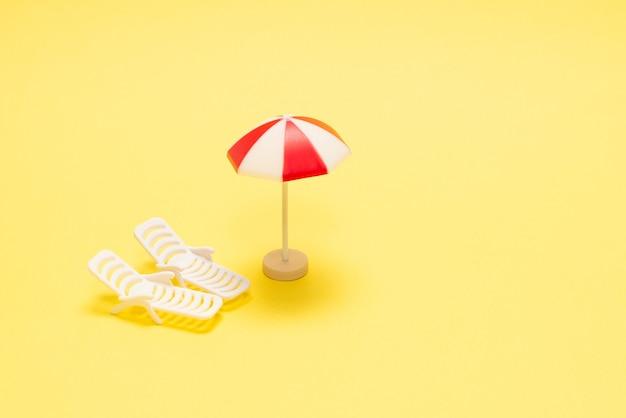 Due lettini e un ombrellone rosso su sfondo giallo. copia spazio.
