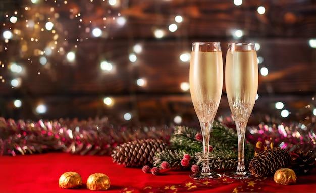 Due sudati bicchieri di champagne, cioccolato e decorazioni natalizie su un tavolo rosso a lato delle ghirlande ardenti.