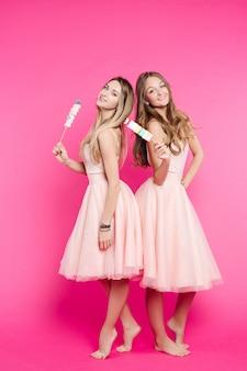 Due ragazze dolci come bambole in posa in rosa con marshmallow.