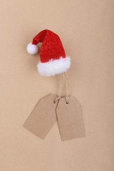 Due etichette di carta kraft riciclata appese a una corda decorata con un cappello da babbo natale