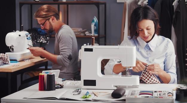 Due sarti che lavorano nel laboratorio di cucito seduti a macchine da cucire, concetto di piccola impresa