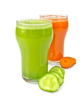 Due bicchieri di succo di carota e cetriolo, fette di verdure isolate su sfondo bianco