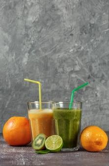Due bicchieri alti di succo d'arancia e un frullato banana-arancia kiwi e spinaci circondati da metà di frutta su uno sfondo grigio cemento. il concetto di perdere peso e una corretta alimentazione.
