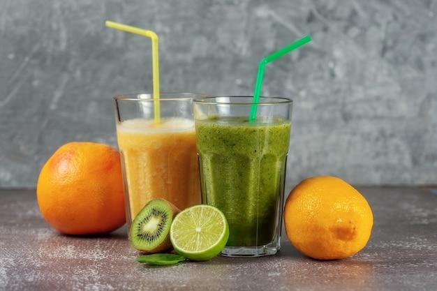 Due bicchieri alti di succo d'arancia e un frullato di kiwi banana arancia e spinaci