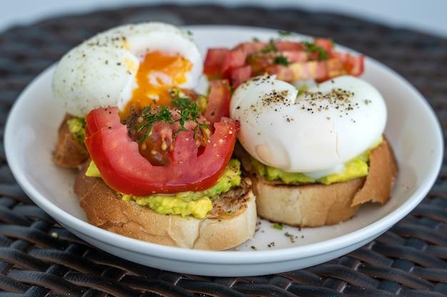 Due gustosi panini con uova sode, avocado verde e pomodoro rosso su piatto bianco, primo piano