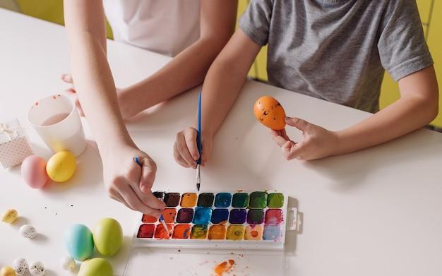 Due figli adolescenti dipingono con acquerelli di uova di pasqua che si preparano per la vacanza. primo piano vista dall'alto.