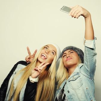 Due amiche adolescenti in abito hipster fanno selfie su un telefono.