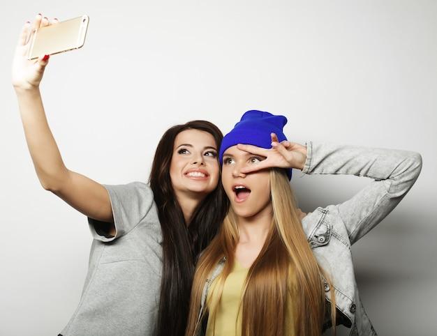 Due amiche adolescenti in abito hipster fanno selfie su una superficie bianca