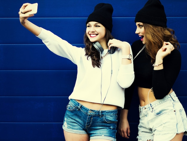 Due amici di ragazze adolescenti in abito hipster all'aperto fanno selfie su un telefono.