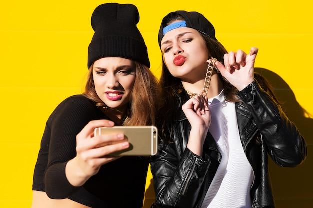 Due amiche adolescenti in abito hipster all'aperto fanno selfie su un telefono.