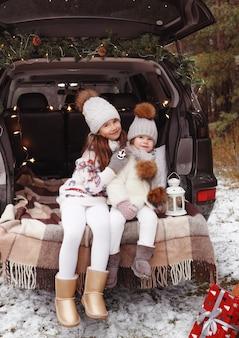 Due ragazze adolescenti si abbracciano nel bagagliaio di un'auto decorata con decorazioni natalizie