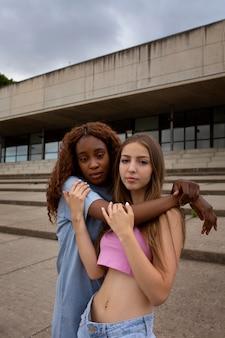 Due ragazze adolescenti in posa insieme mentre trascorrono del tempo all'aperto