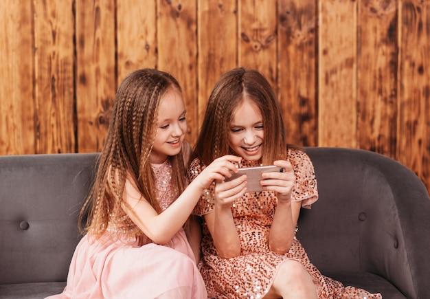 Due ragazze adolescenti si siedono sul divano e guardano lo schermo dello smartphone