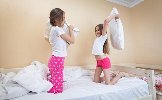 Due sorelle adolescenti in pigiama si divertono a combattere con i cuscini in camera da letto