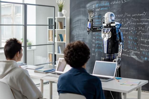 Due studenti adolescenti seduti alla scrivania alla lezione di tecnologia moderna e guardando il robot che dimostra le sue capacità dalla lavagna