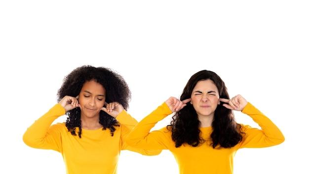 Due ragazze dell'adolescente che coprono le sue orecchie isolate su una priorità bassa bianca