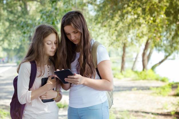 Due ragazze sorridenti dell'adolescente con gli zaini