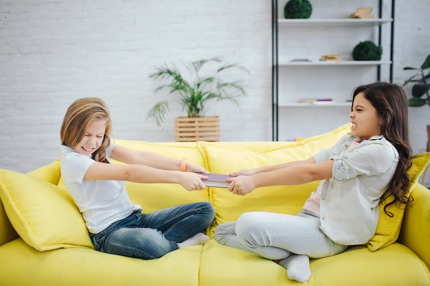 Due adolescenti si siedono sul divano giallo nella sala. combattono il taccuino di abete. ogni ragazza lo tira a sé. lottano.