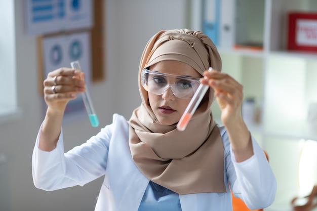 Due provette. chimico femminile dagli occhi scuri con gli occhiali che tengono due provette con liquidi
