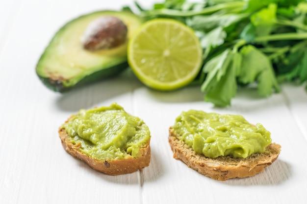 Due fette sottili di pane con guacamole su un tavolo di legno bianco. dieta vegetariana cibo messicano avocado. cibo crudo.