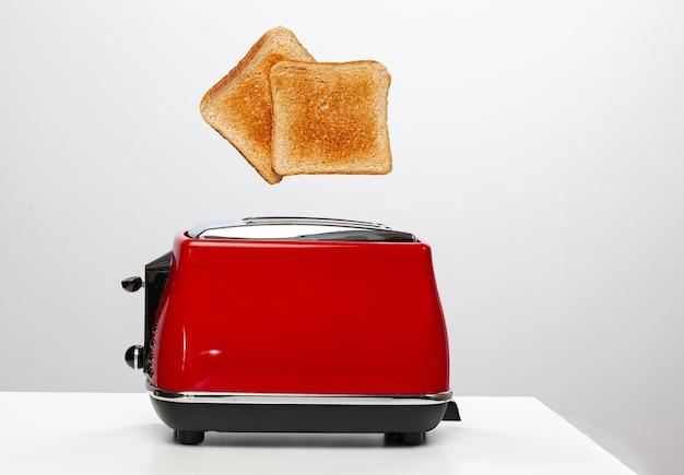 Due toast che saltano dal tostapane elettrico rosso su bianco