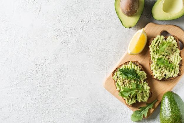 Due toast con avocado e insalata verde a colazione su sfondo bianco