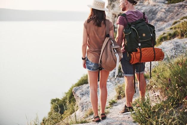 Due maschio e una donna turistica con gli zaini stanno alla cima della montagna e godono dell'alba. concetto di vacanze avventura stile di vita di viaggio