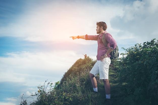Due turisti con zaini godendo tramonto sulla cima di una montagna