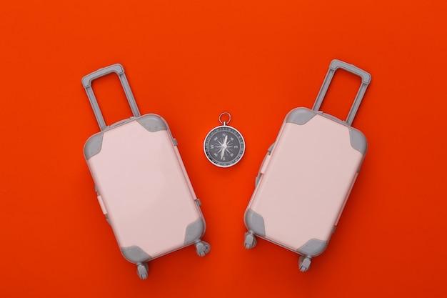 Due bagagli da viaggio giocattolo, bussola sull'arancia. pianificazione del viaggio