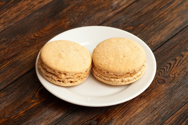 Due macarons francesi tradizionali del cioccolato sul piatto, tavola di legno