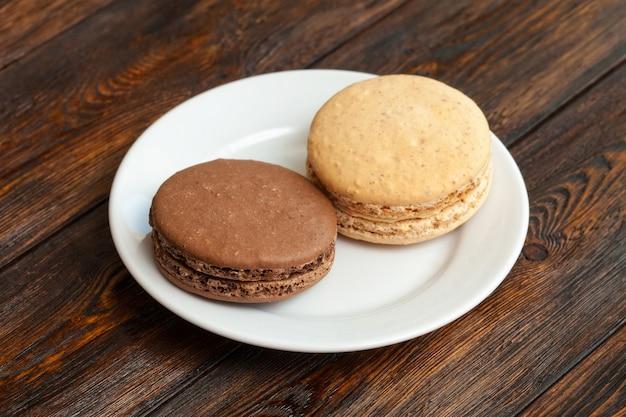 Due macarons francesi tradizionali del cioccolato sul piatto, parete di legno