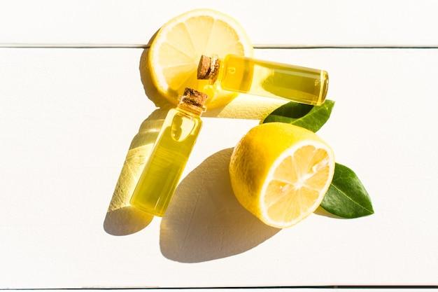 Due bottiglie trasparenti con coperchio in sughero con olio di limone aromatico su un tavolo di legno bianco. sezhiy limone e foglie verdi. luce del sole.
