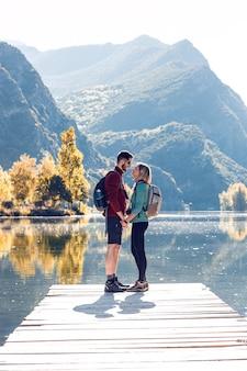 Due escursionisti di viaggio innamorati che si baciano davanti al lago in montagna.